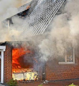 Garagenbrand greift auf Wohnhaus über - Großeinsatz in Nordhorn Bei einem Großbrand in Nordhorn wurden am Samstagnachmittag eine Garage und ein angrenzendes Wohnhaus erheblich beschädigt. Zwei Personen kamen mit Verletzungen in ein Krankenhaus. Um 13.43 Uhr wurde die Ortsfeuerwehr Nordhorn am Samstag, den 10. Oktober 2015 mit einem B3-Alarm (Mittelbrand) in den Stadtteil Neuberlin gerufen. Gemeldet war in der Kölner Straße zunächst ein Garagenbrand. Doch schon auf der Anfahrt konnte der Brandmeister vom Dienst (BvD) eine erhebliche Rauchentwicklung ausmachen, so dass er gleich die Ortsfeuerwehr Brandlecht nachalarmierten ließ. Eine gute und richtige Entscheidung, denn als der BvD an der Einsatzstelle ankam, stand die Garage bereits in Vollbrand. Die Flammen hatten bereits auf das Dach und das Innere des Hauses übergegriffen. Die fünf Bewohner des Hauses waren in Sicherheit, zwei von ihnen mussten jedoch mit dem Rettungswagen in die Nordhorn Euregio-Klinik verbracht werden. Ein Bewohner hatte offenbar noch Löschversuche unternommen und sich dabei Brandverletzungen und eine Rauchgasintoxikation zugezogen, eine Frau kamen ebenfalls in die Klinik.